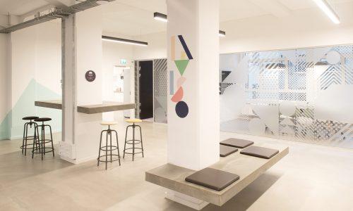 Reception i virksomhed med specialdesignet venteområde, siddepladser og grafik.